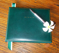 Guest book sitting on a dark wood table with pen at the ready